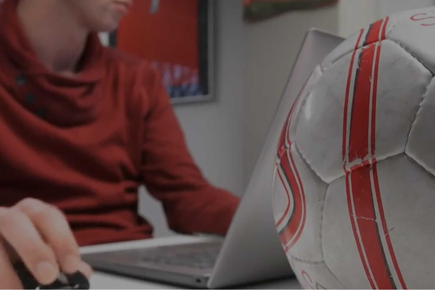SCIS sport employee working on laptop with soccer ball